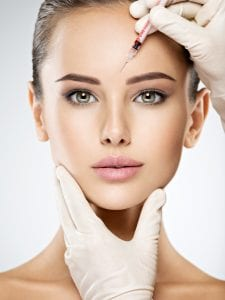 Woman Getting Cosmetic Botox Injection In Forehead