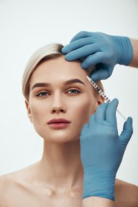 Young pretty woman gettingbotox injection in her face